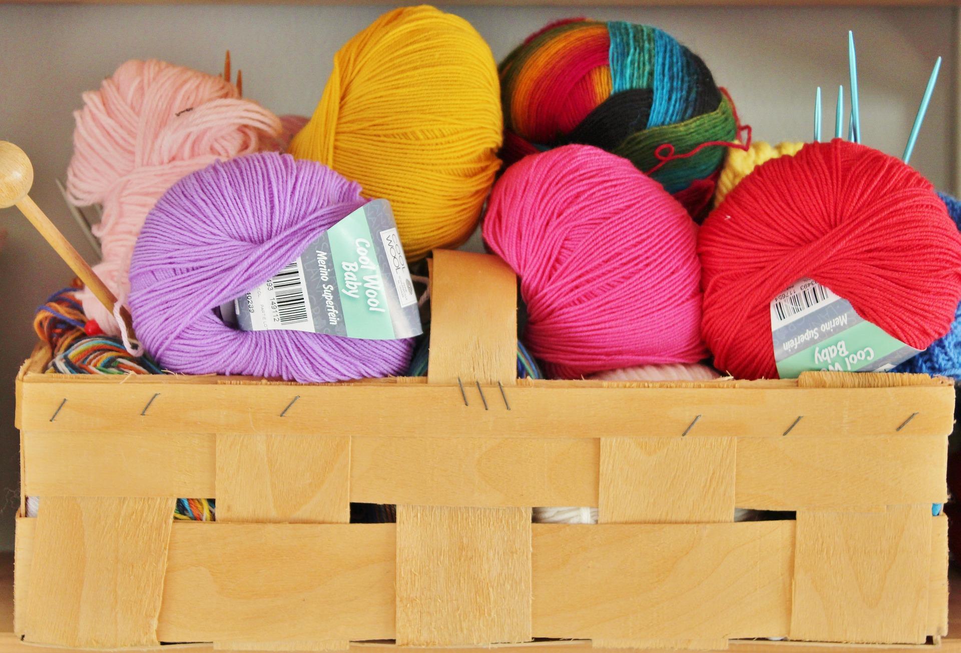 bolletjes wol in verschillende kleuren in mand met breinaalden